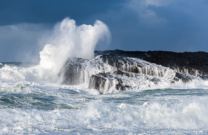 Waves crashing against limestone sea cliff