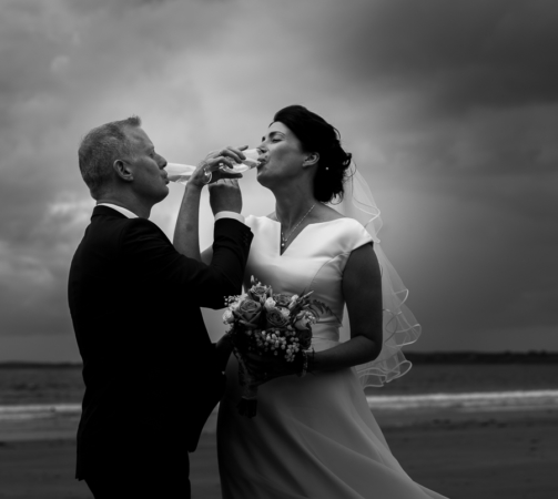 Wedding couple drinking champagne on a beach